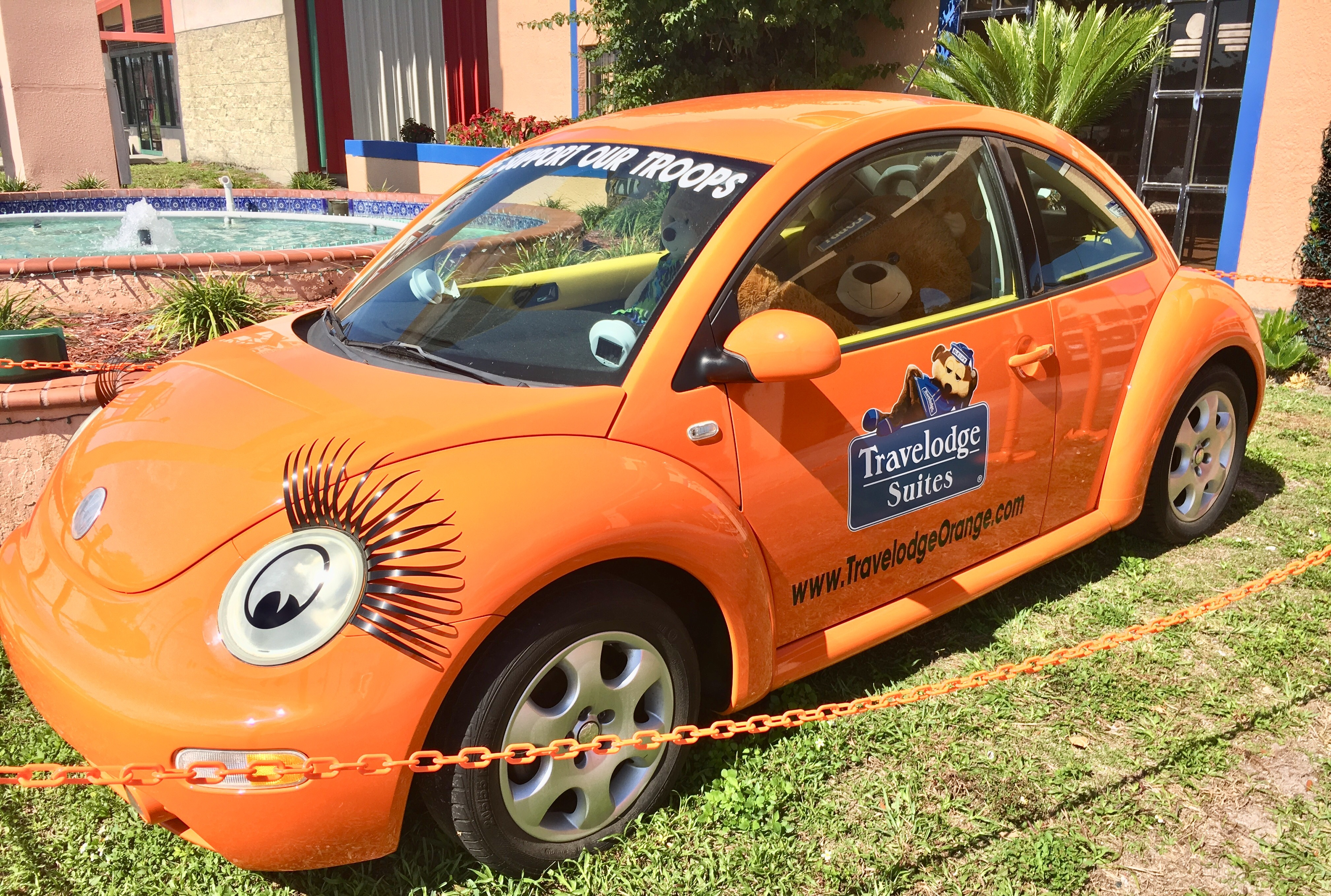 Parked in front of the Travelodge is a bright orange Volkswagen Beetle